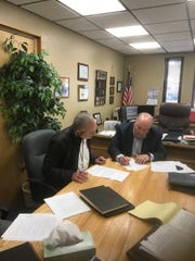 Lawrence Heller of Acme Equities LLC, left, and Farmington City Manager Rob Mayes, right, sign an agreement that will allow Farmington to keep the San Juan Generating Station open after 2022.