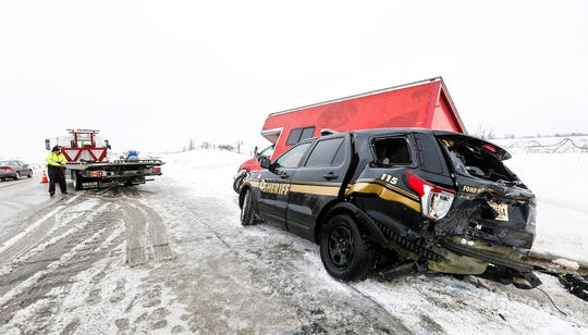 A tow truck operator gets ready to load a Fond du Lac County Sheriff's Office squad car that was involved in a three-vehicle crash Sunday   near County Highway F south of Fond du Lac. High winds and blowing snow caused near whiteout conditions in parts of the state.