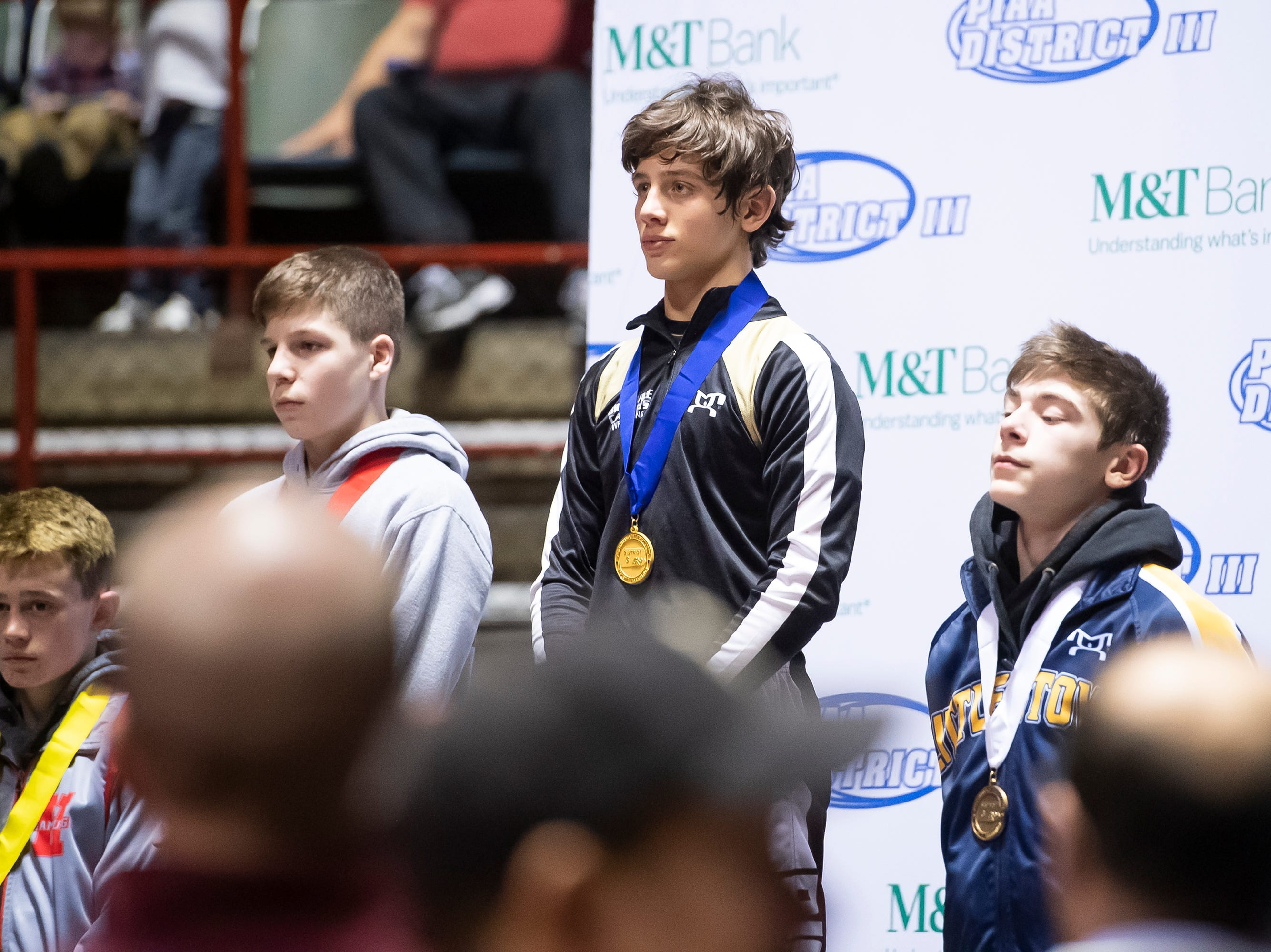 Biglerville's Levi Haines, center, and Littlestown's Connor Brown, right, stand on the podium after placing first and third, respectively, at the District 3 wrestling championships at Hersheypark Arena Saturday, February 23, 2019.