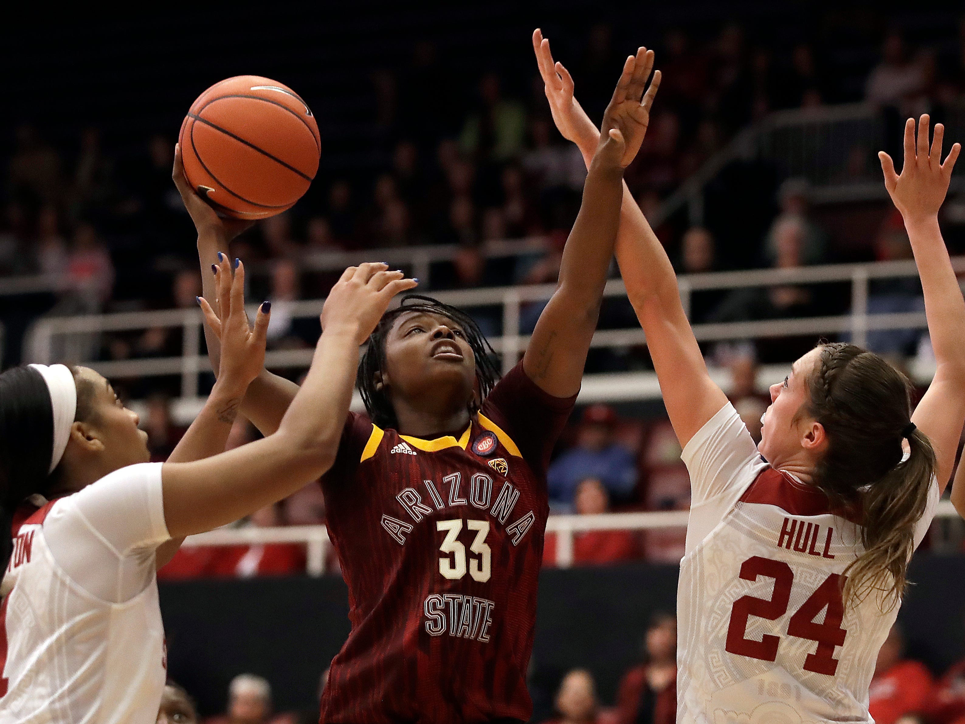Arizona State's Charnea Johnson-Chapman (33) shoots between Stanford's DiJonai Carrington, left, and Lacie Hull (24) during the first half of an NCAA college basketball game Sunday, Feb. 24, 2019, in Stanford, Calif.