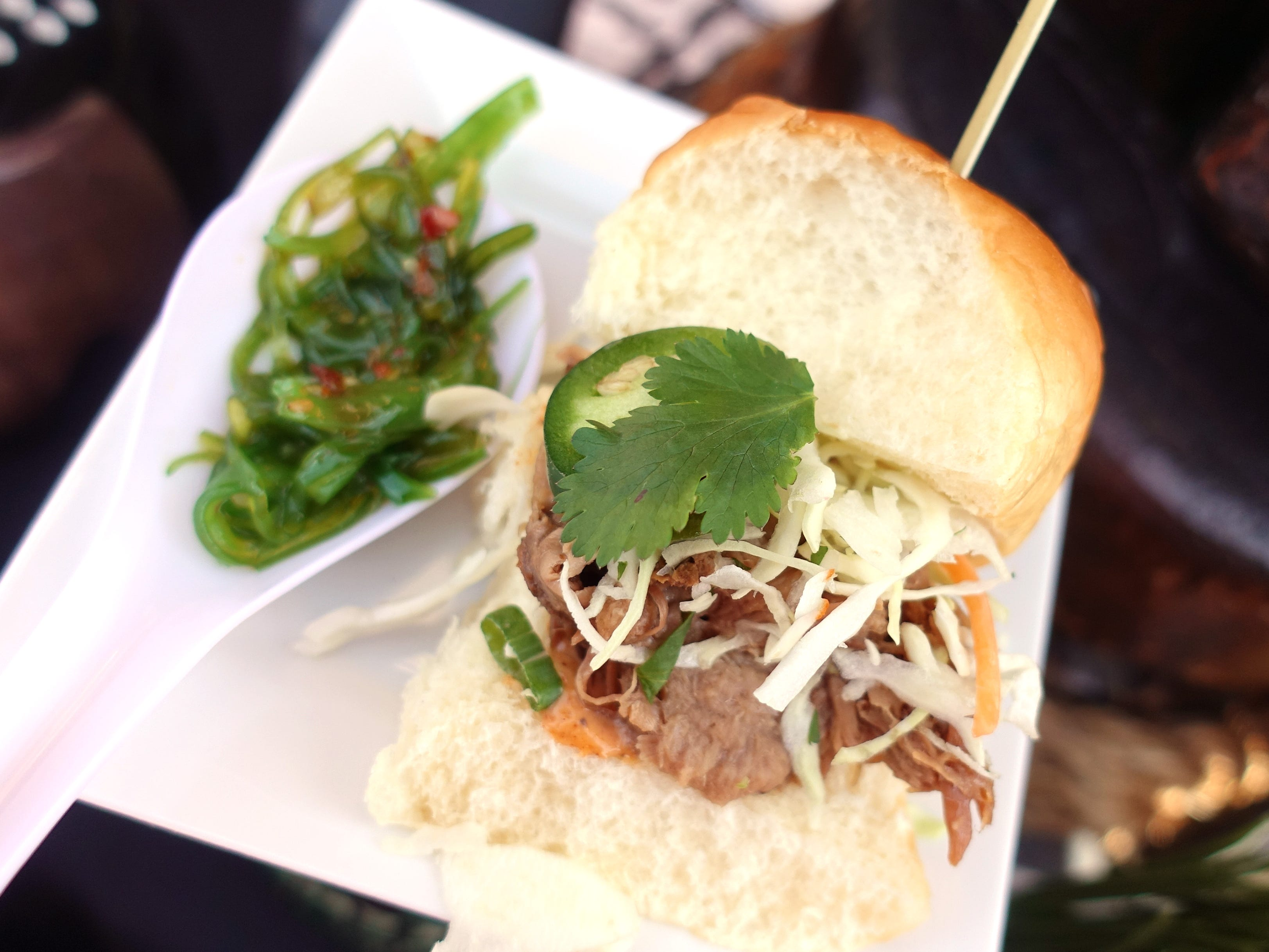 Hilo slider with luau pork, Asian slaw, cilantro, jalapeno, chile lime aioli, Sriracha, Hawaiian bun and spicy seaweed salad from Hula's Modern Tiki at the 2019 Devour Culinary Classic at the Desert Botanical Garden in Phoenix.