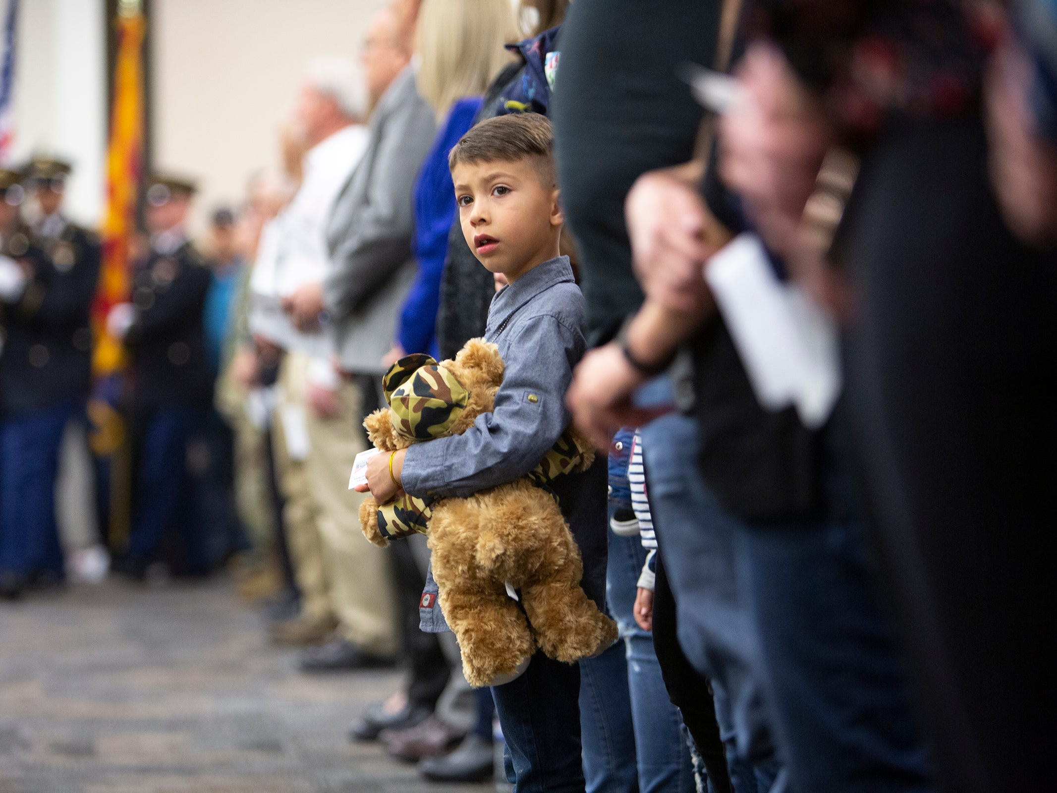"""A child standing in the front row holds a """"battalion buddy"""" stuffed animal at the deployment ceremony for the 253rd Engineer Battalion at Papago Park Military Reservation on Sunday, Feb. 24, 2019. The battalion buddies were distributed by Operation Gratitude volunteers."""