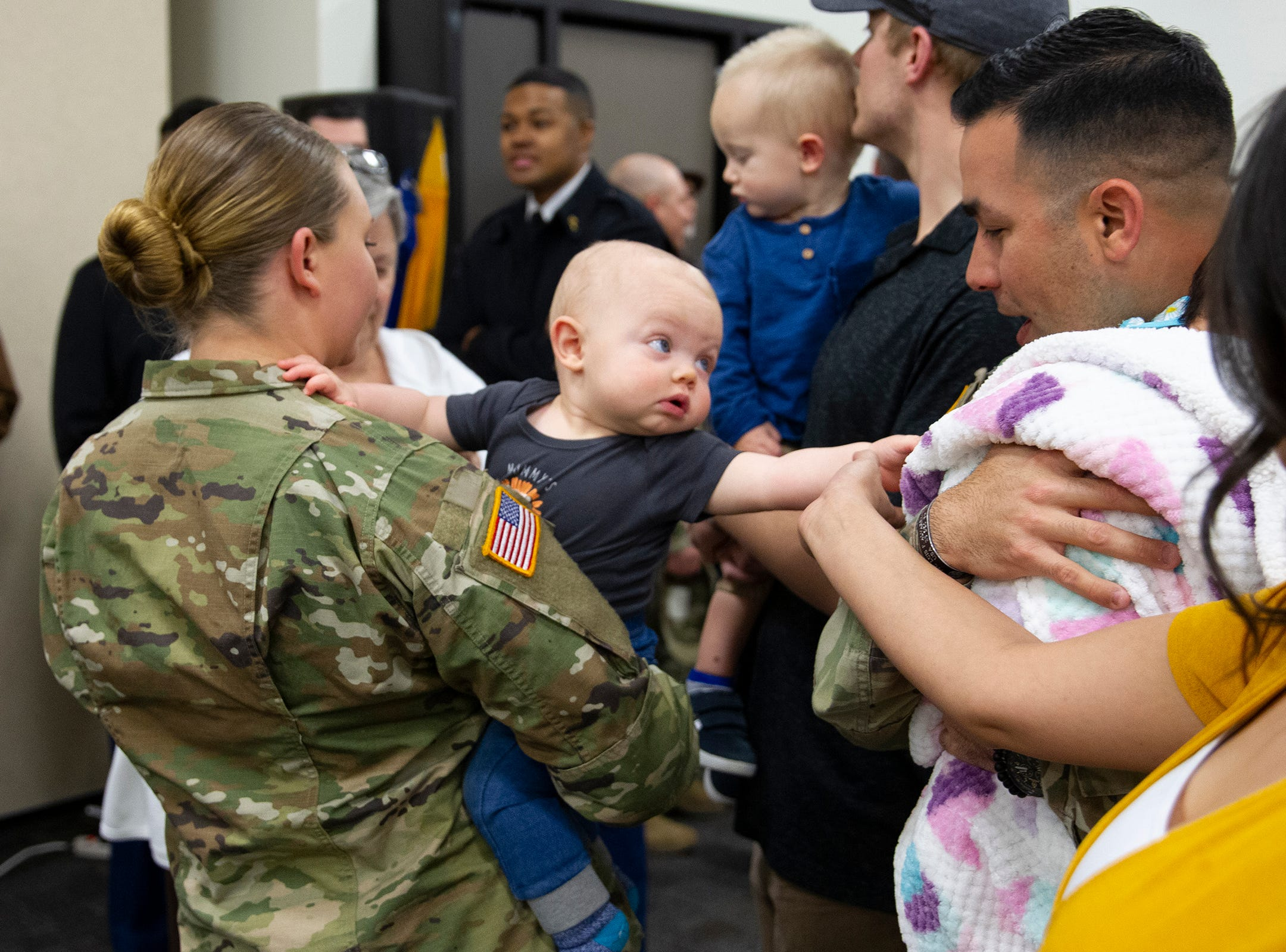 Sgt. Cassidy Presmyk's son Logan reaches out to another military baby before the deployment ceremony for the 253rd Engineer Battalion at Papago Park Military Reservation on Sunday, Feb. 24, 2019.
