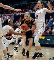 Arizona State's Courtney Ekmark, center, keeps the ball from Stanford's DiJonai Carrington, left, and Alanna Smith, right, during the first half of an NCAA college basketball game Sunday, Feb. 24, 2019, in Stanford, Calif.