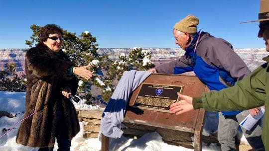 American Society of Civil Engineers President Robin Kemper reaches for a handshake as Jonathan Upchurch, an ASCE Fellow, unveils a plaque commemorating the South Kaibab Suspension Bridge's designation as a National Historic Civil Engineering Landmark.