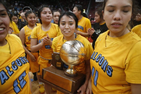 Alchesay's Shalicia Colelay (5) carries the trophy with her teammates after winning the 2A girls basketball state championship game over Scottsdale Christian at Gila River Arena in Glendale, Ariz. on February 23, 2019.