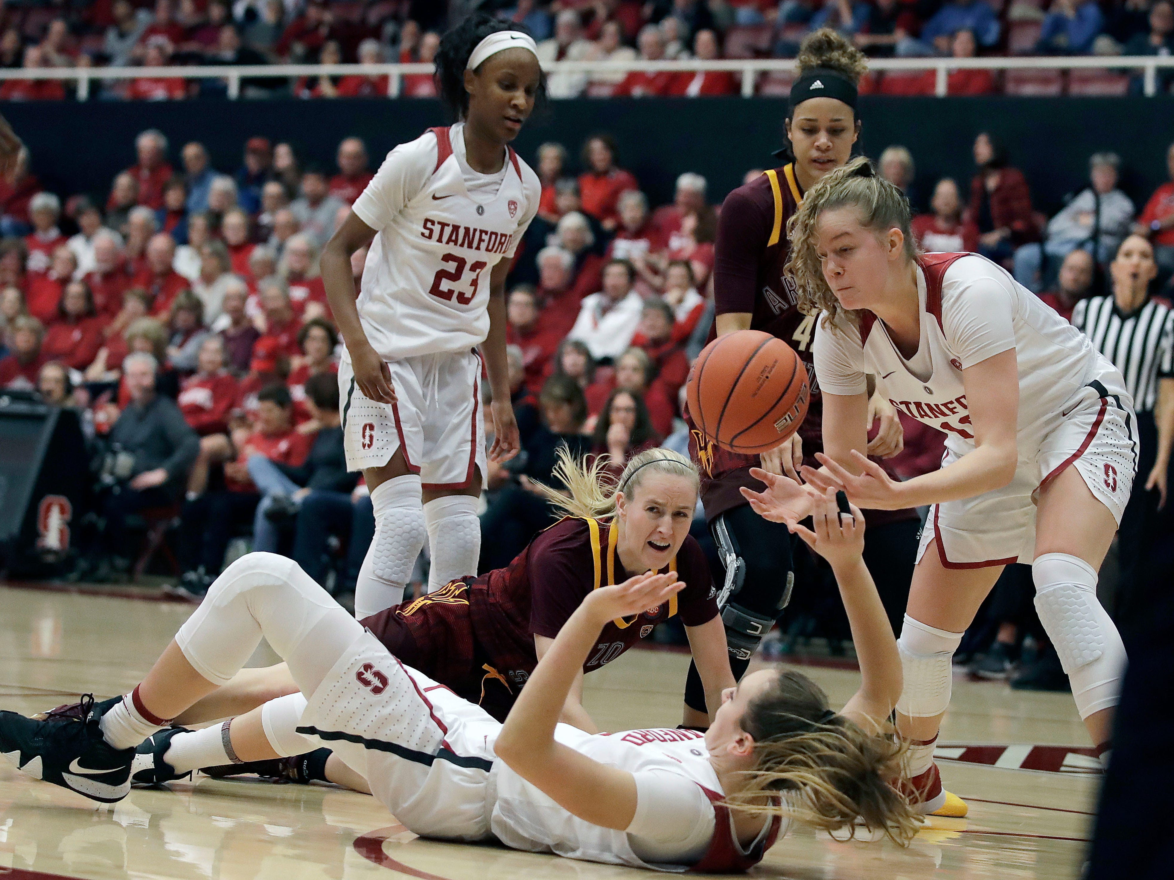 Stanford's Alyssa Jerome, right, reaches for a loose ball between Arizona State's Courtney Ekmark and Alanna Smith, foreground on floor, during the first half of an NCAA college basketball game Sunday, Feb. 24, 2019, in Stanford, Calif.