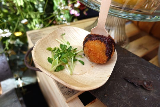 Split pea arancino with Carnaroli risotto, smoked mozzarella, pecorino crema, balsamic reduction and pea sprouts from The Parlor at the 2019 Devour Culinary Classic at the Desert Botanical Garden in Phoenix.