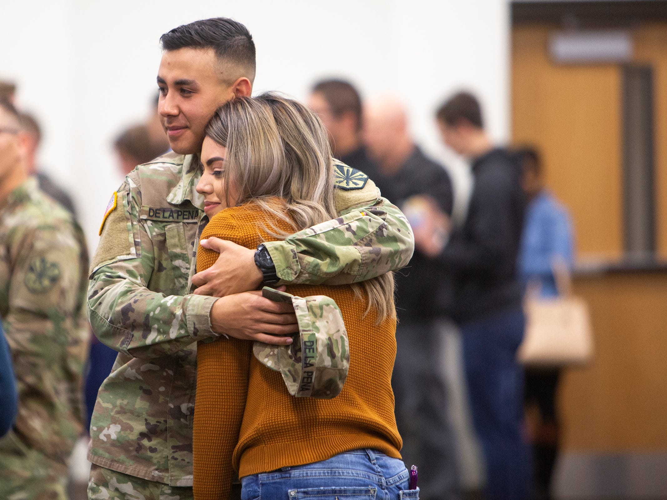 Spc. Edgar De La Peña gives a hug to his girlfriend of five years, Fabiola Burciaga, before the deployment ceremony for the 253rd Engineer Battalion at Papago Park Military Reservation on Sunday, Feb. 24, 2019. The soldiers boarded buses immediately after the ceremony.