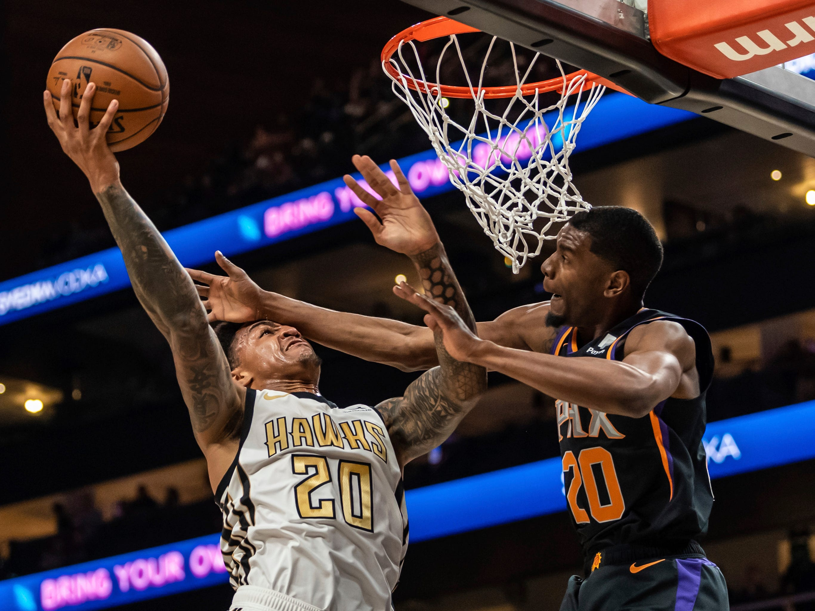 Atlanta Hawks forward John Collins (20) shoots as Phoenix Suns forward Josh Jackson (20) defends during the first half of an NBA basketball game Saturday, Feb. 23, 2019, in Atlanta.