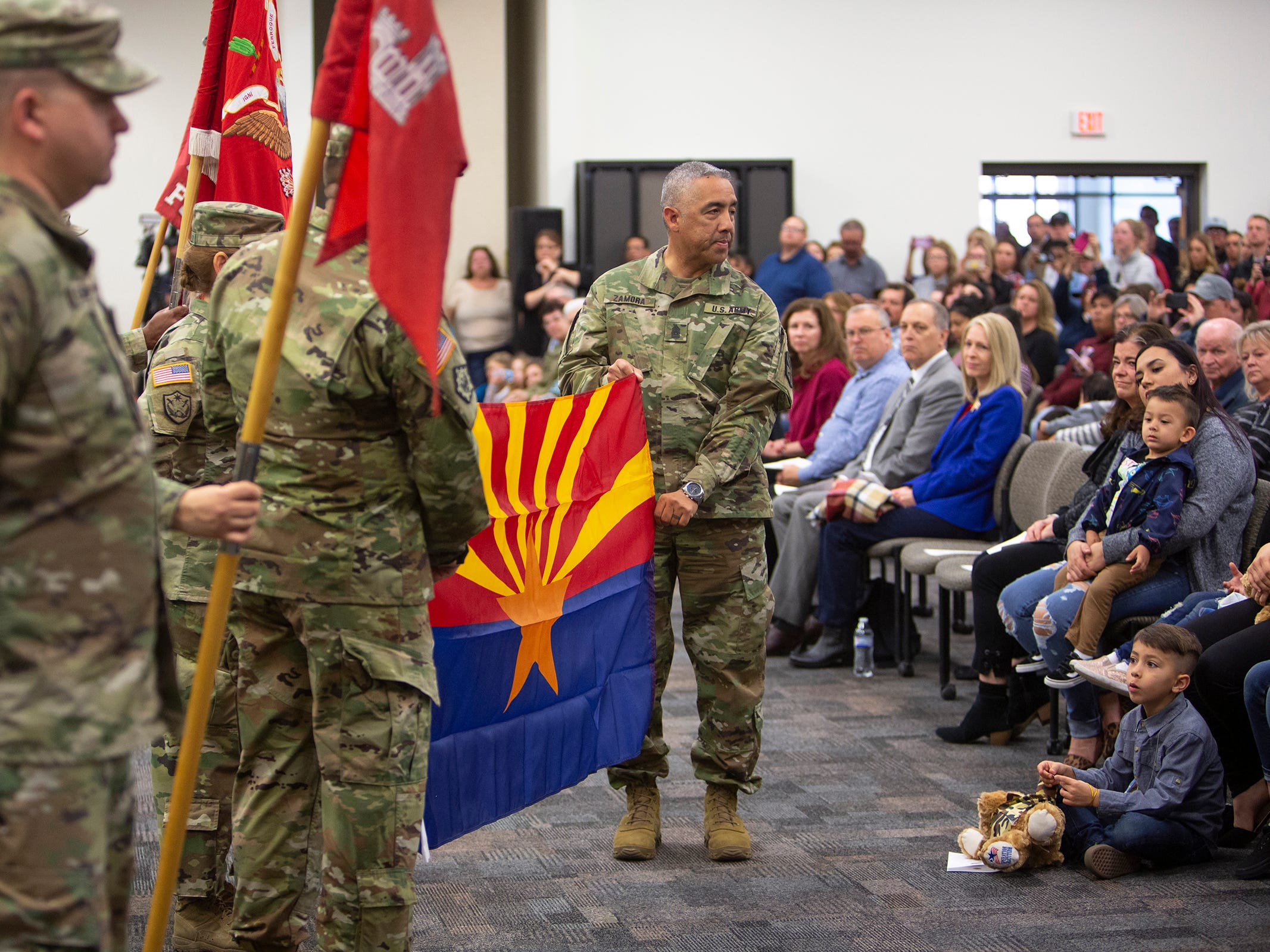Lt. Col. Peggy Grunewald (not seen) and Maj. Fidel Zamora (right) hold the Arizona flag during the deployment ceremony for the 253rd Engineer Battalion at Papago Park Military Reservation on Sunday, Feb. 24, 2019.