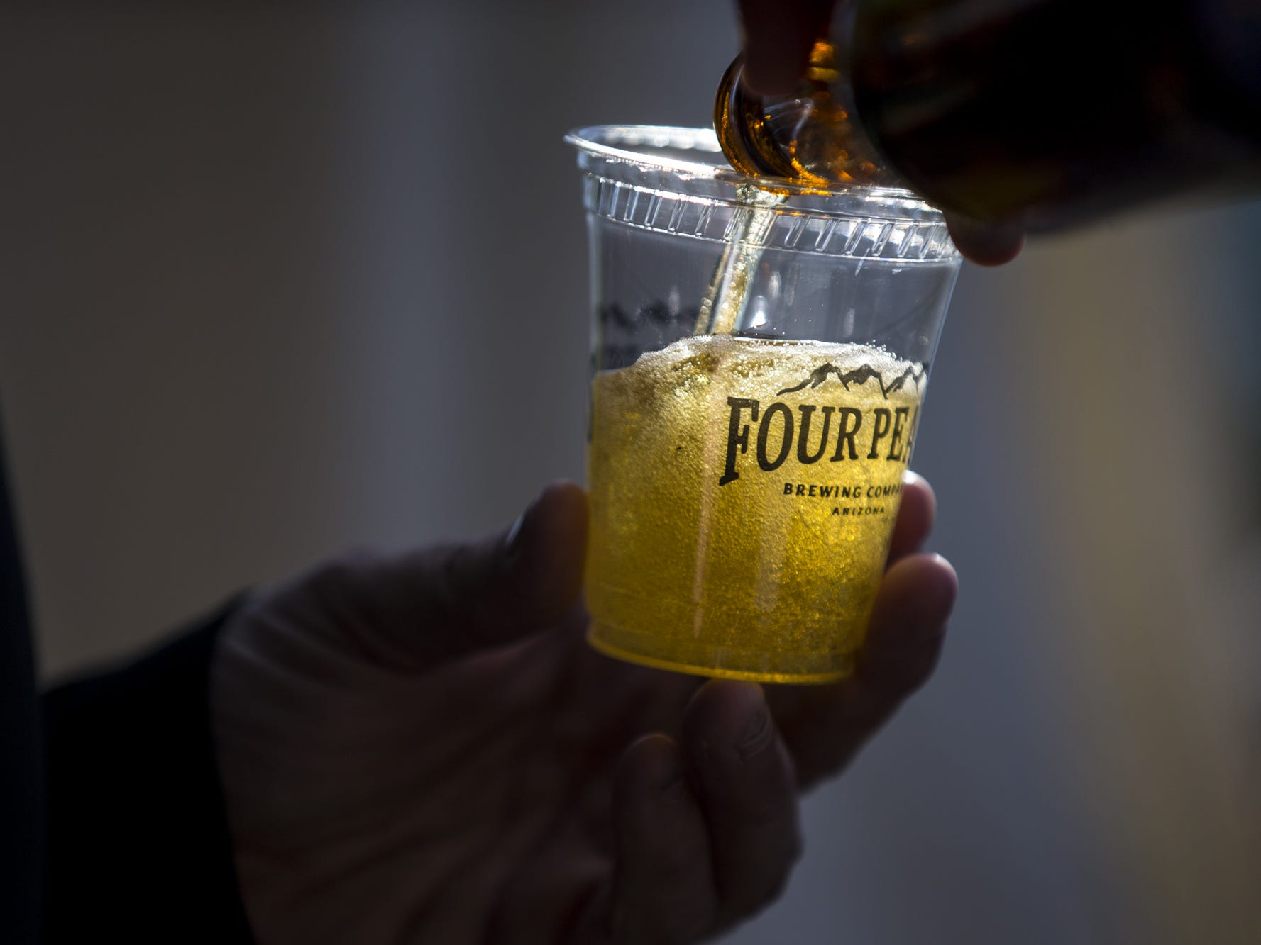Jon Schmidt of Four Peaks Brewing pours a beer sample during Day 1 of the Devour Culinary Classic on Saturday, Feb. 23, 2019, at Desert Botanical Garden in Phoenix.