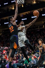 Atlanta Hawks forward Taurean Prince (12) goes in for a layup past Phoenix Suns center Deandre Ayton (22) during the first half of an NBA basketball game Saturday, Feb. 23, 2019, in Atlanta.