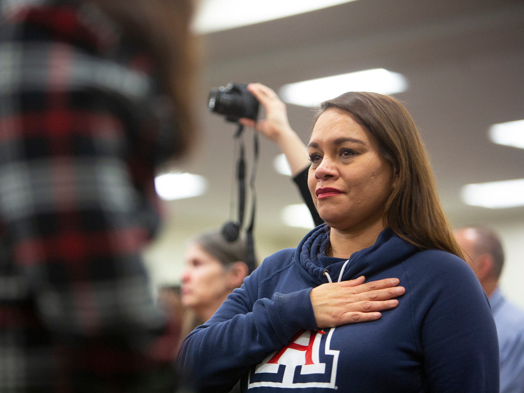 Irene Corella places her hand on her chest for the national anthem during the deployment ceremony for the 253rd Engineer Battalion at Papago Park Military Reservation on Sunday, Feb. 24, 2019.
