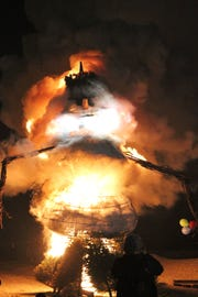 Virgil, the 25-foot-snowman covered with Crisco and candle wax, goes up in flames on Saturday night in Port Clinton.
