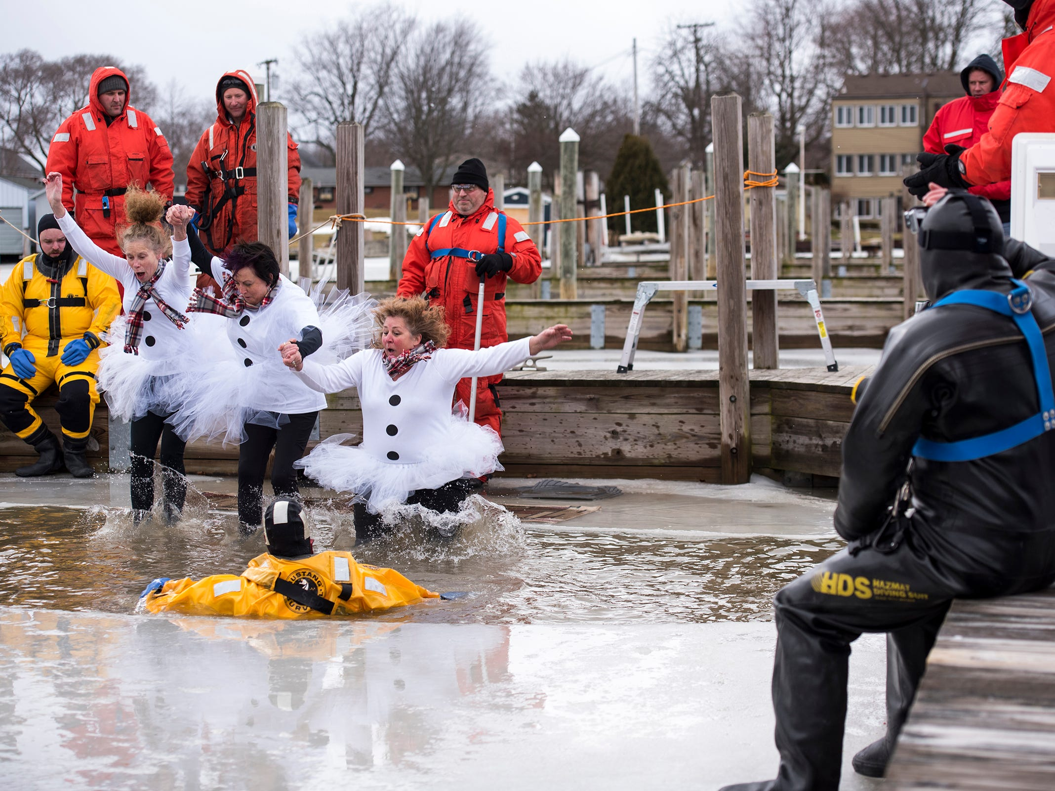 Participants react to the frigid water as they plunge through a hole cut in the ice in the St. Clair Boat Harbor Sunday, Feb. 24, 2019 for the annual St. Clair Polar Plunge.