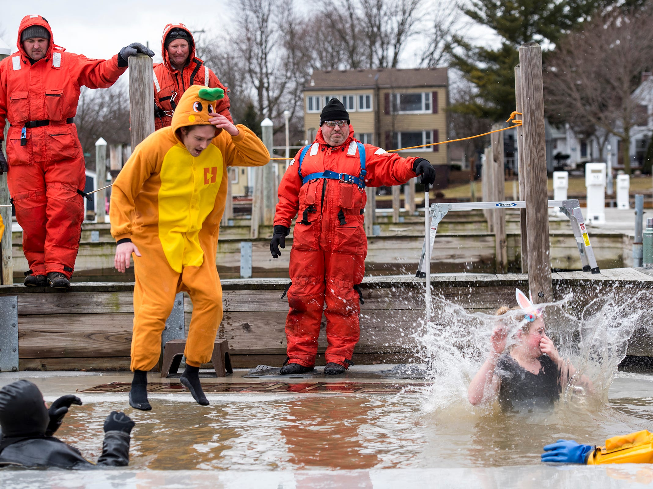 Brianna Thurston, right, and Bryan Nowak, dressed as a rabbit and a carrot, plunge into the water in the St. Clair Boat Harbor Sunday, Feb. 24, 2019 during the annual St. Clair Polar Plunge.
