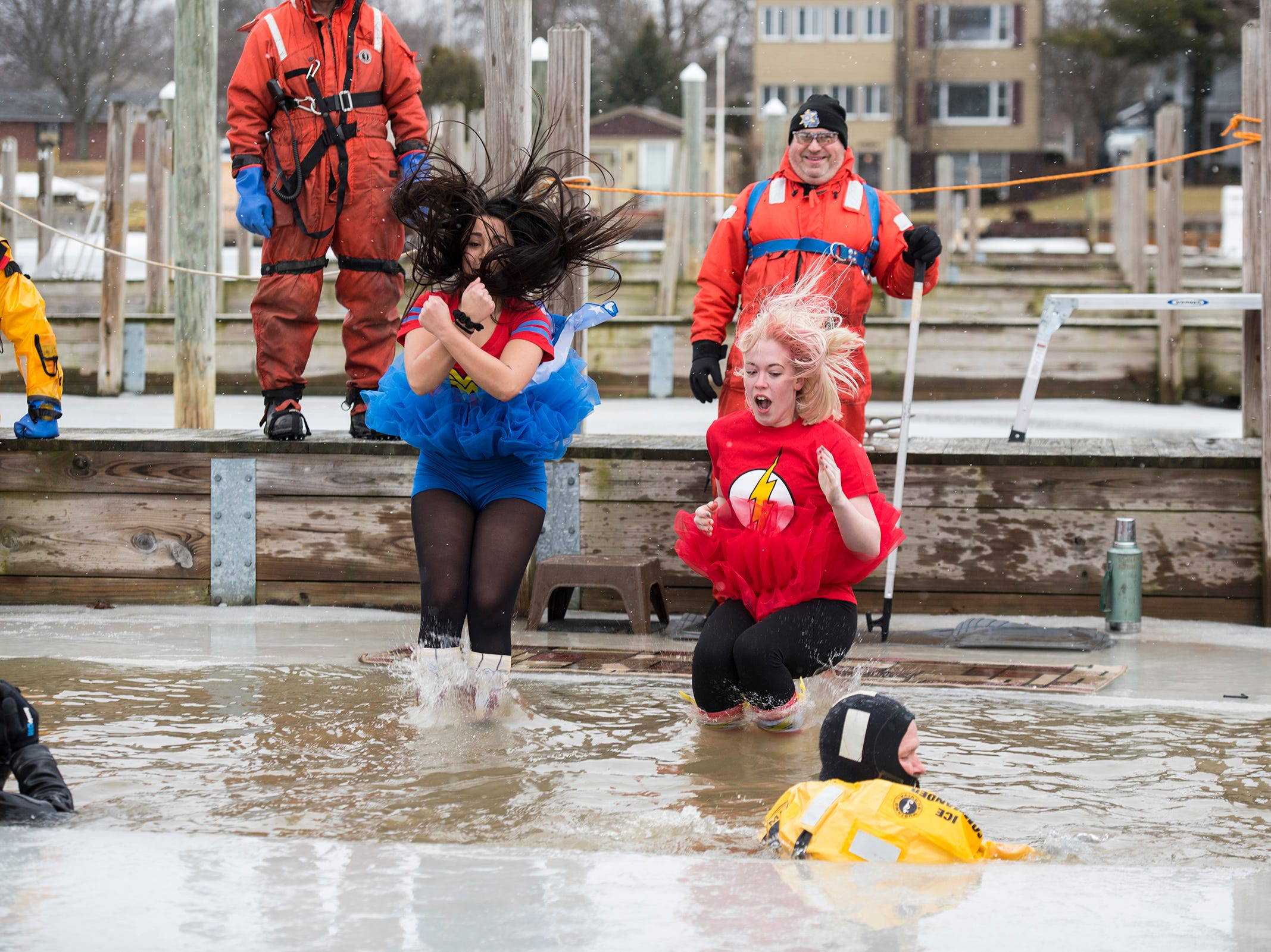 Plungers dressed as Wonderwoman and The Flash jump into the water in the St. Clair Boat Harbor through a hole cut in the ice  Sunday, Feb. 24, 2019 for the annual St. Clair Polar Plunge.
