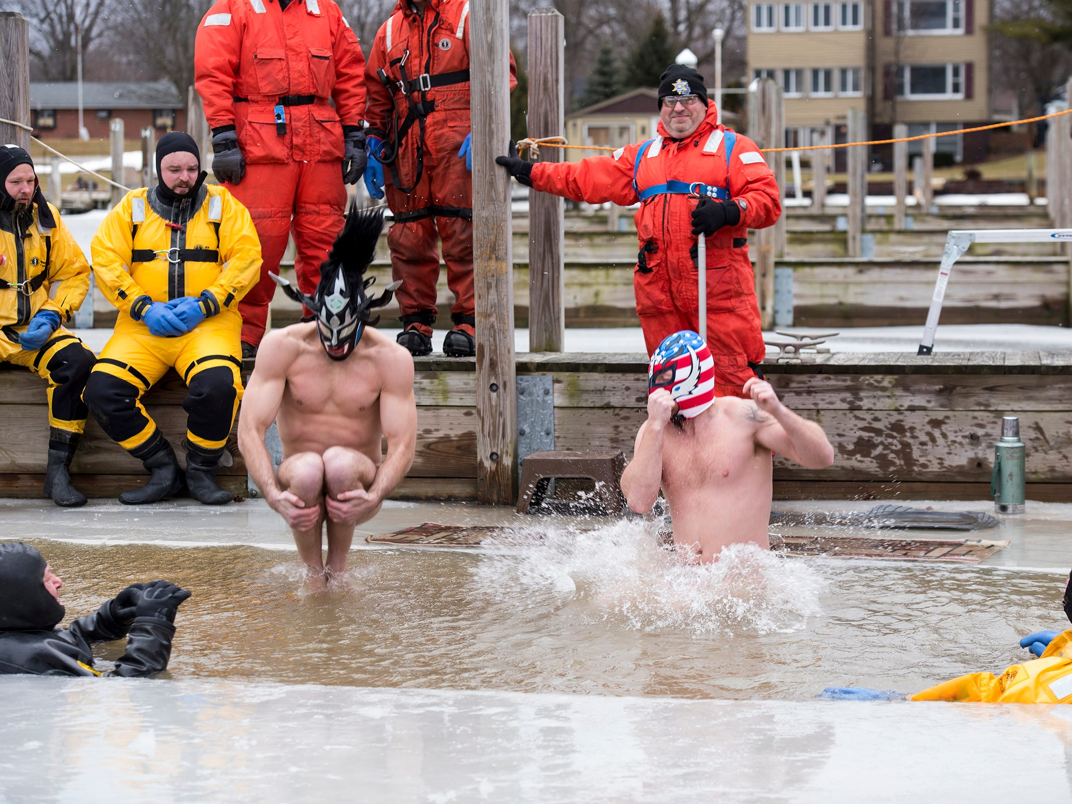 Sergio Hernandez, left, and Ryan Teeple plunge through a hole in the ice into the water in the St. Clair Boat Harbor Sunday, Feb. 24, 2019 during the annual St. Clair Polar Plunge.