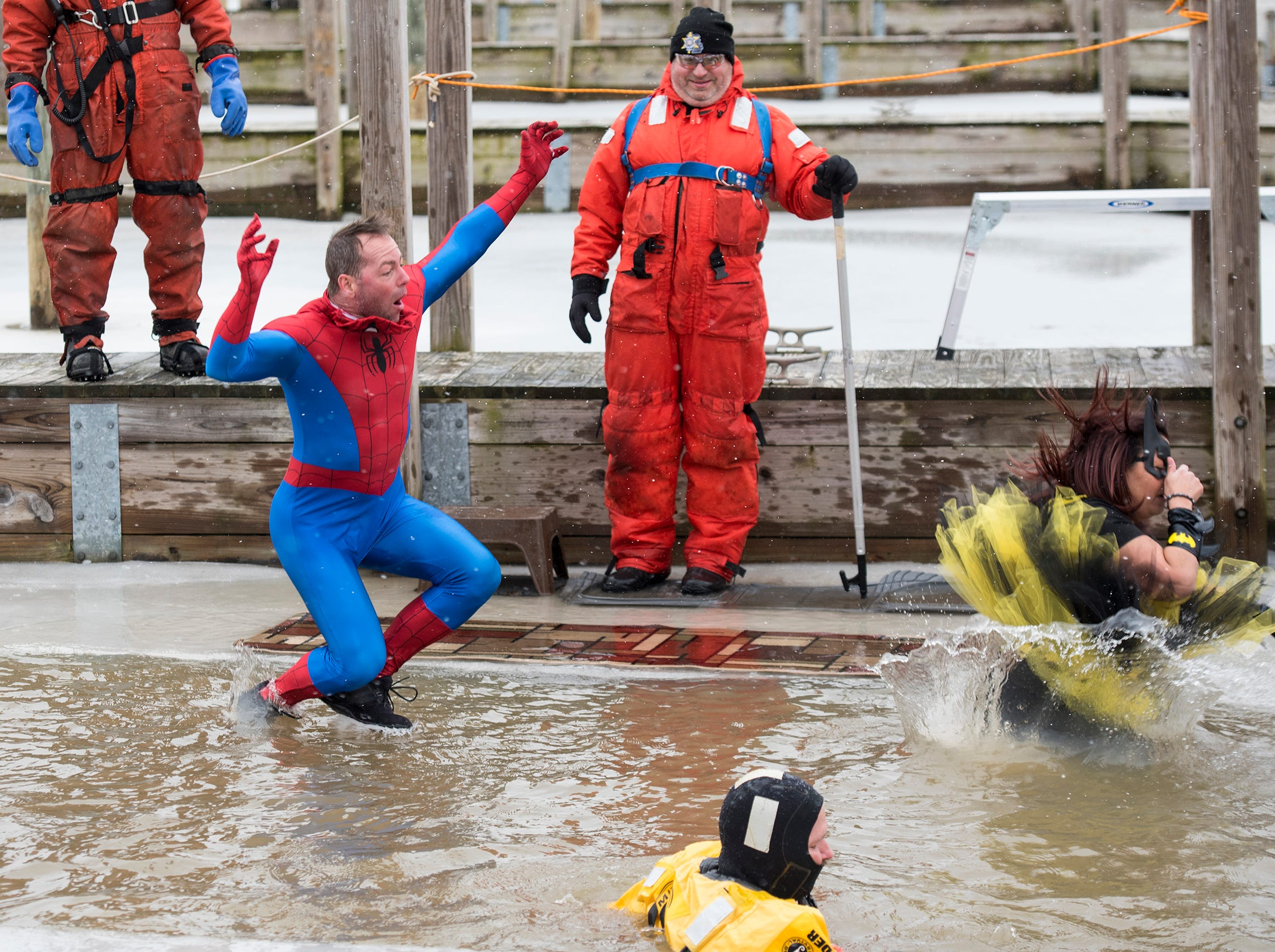 Plungers dressed as Spiderman and Bat Woman jump into the water in the St. Clair Boat Harbor through a hole cut in the ice  Sunday, Feb. 24, 2019 for the annual St. Clair Polar Plunge.