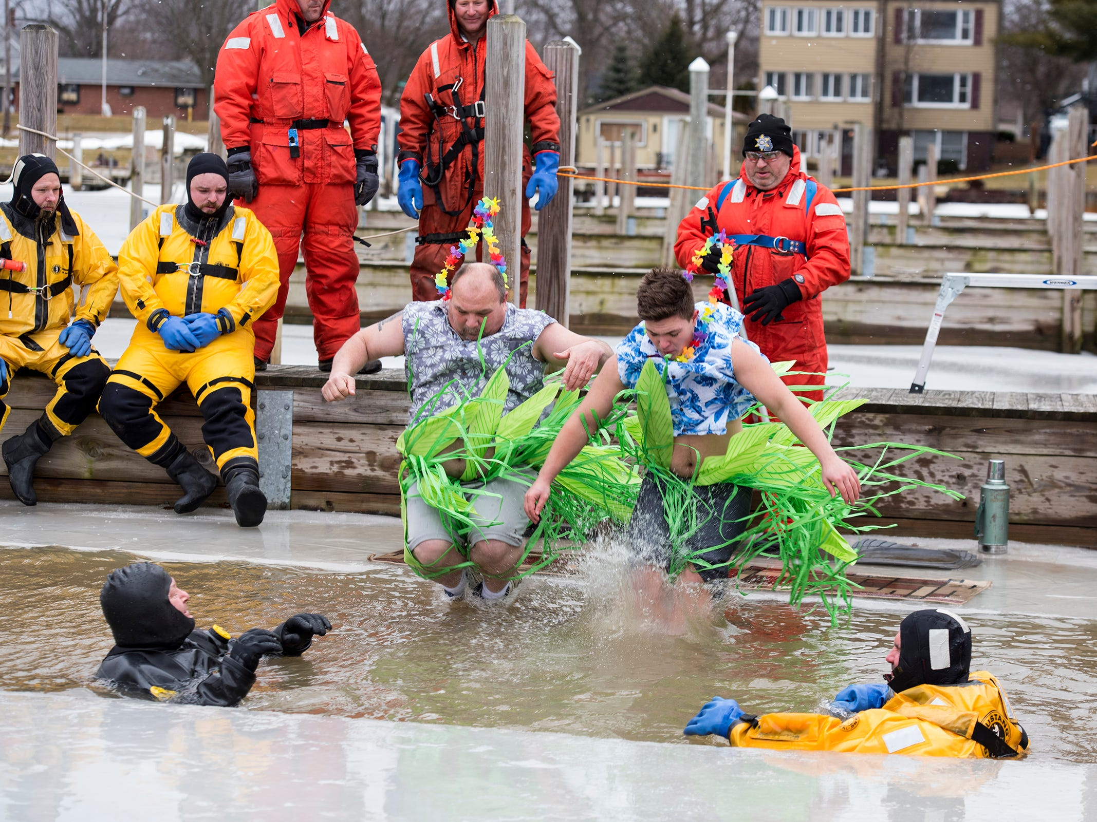 Participants plunge through a hole cut in the ice in the St. Clair Boat Harbor Sunday, Feb. 24, 2019 for the annual St. Clair Polar Plunge.