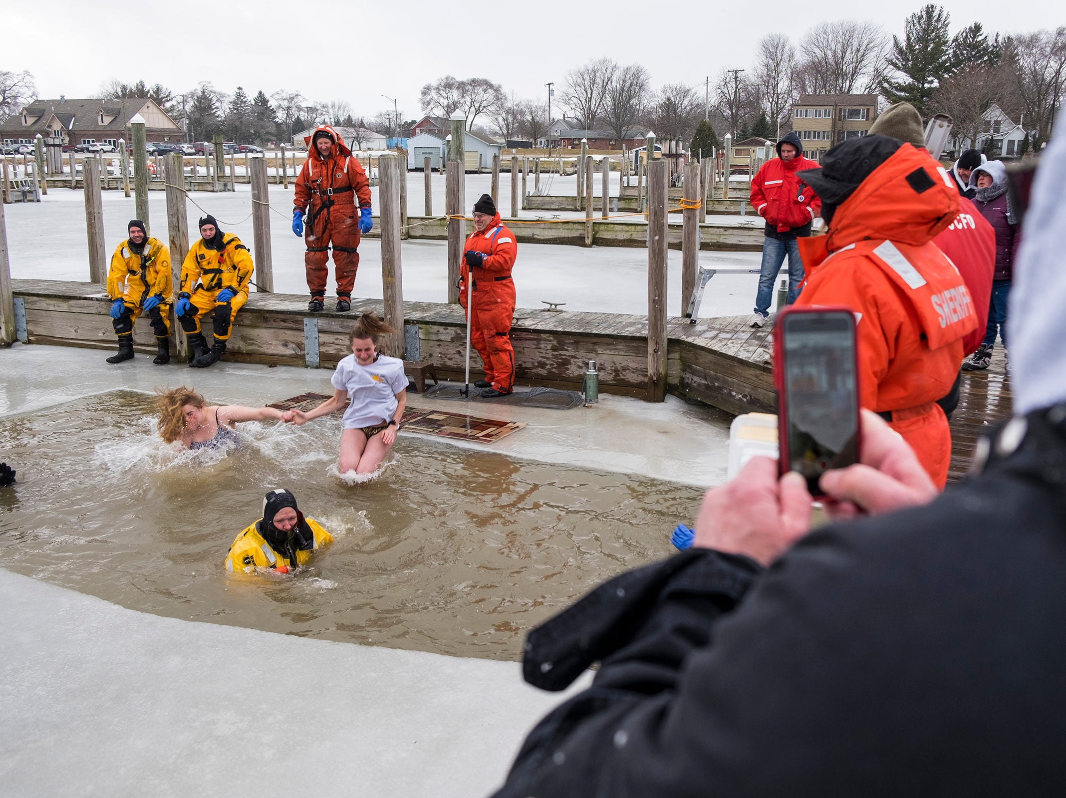 Johnny Carter, right, takes pictures on a cell phone while Krista Stolicker and Lauren Kramer plunge into the water in the St. Clair Boat Harbor Sunday, Feb. 24, 2019 during the annual St. Clair Polar Plunge.