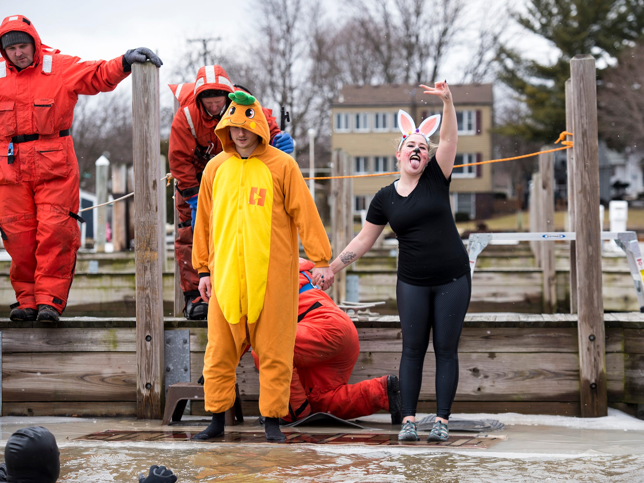 Brianna Thurston, dressed as a rabbit, strikes a pose while holding hands with Bryan Nowak,, who is dressed as a carrot, before they jump into the St. Clair Boat Harbor Sunday, Feb. 24, 2019 during the annual St. Clair Polar Plunge.