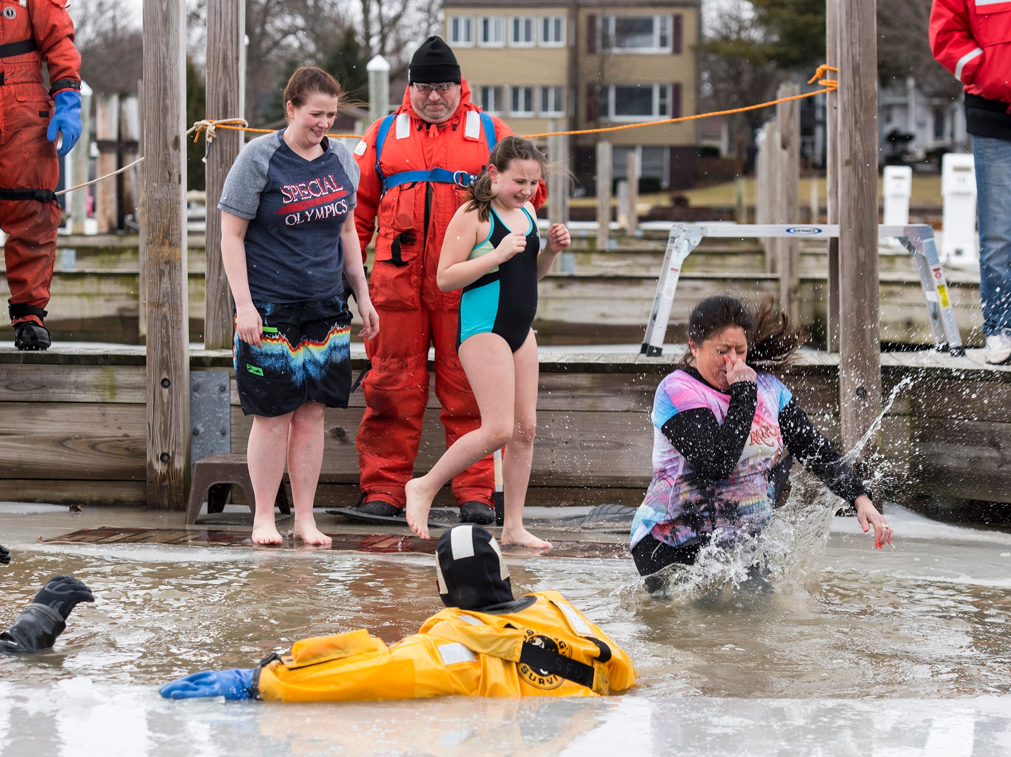 Audrey Bishop, right, and Olovia Doherty, center, watch as Theresa Kean plunges into the St. Clair Boat Harbor Sunday, Feb. 24, 2019 during the annual St. Clair Polar Plunge.