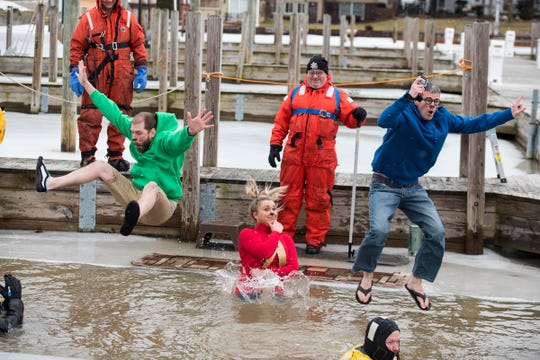 Plungers dressed as Alvin and the Chipmunks jump through a hole cut in the ice in the St. Clair Boat Harbor Sunday, Feb. 24, 2019 for the annual St. Clair Polar Plunge.
