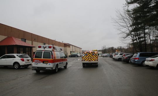 Emergency vehicles leave Gold's Gym on Sunday after a reported fire inside a maintenance room that left two with minor injuries.