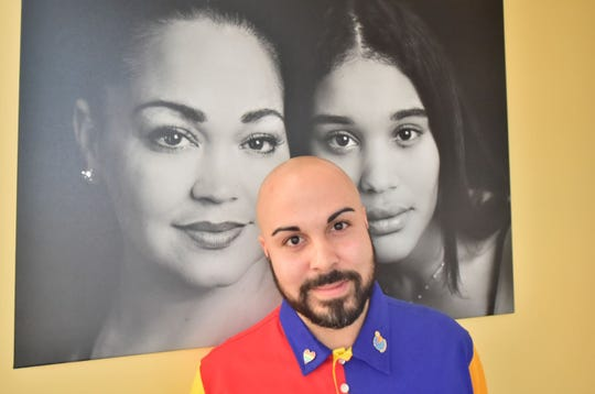 "Chambersburg photographer poses in front of a portrait of a mother and daughter that is featured in his exhibit, ""Black Girl Magic,"" on display through March 31 at Coyle Free Library, Chambersburg. Pictured on Friday, Feb. 22, 2019."