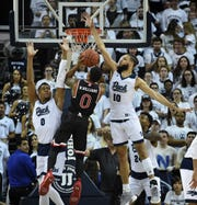 Nevada's Tre' Shawn Thurman, left, and Caleb Martin defend against Fresno State's New Williams on Saturday at Lawlor Events Center.