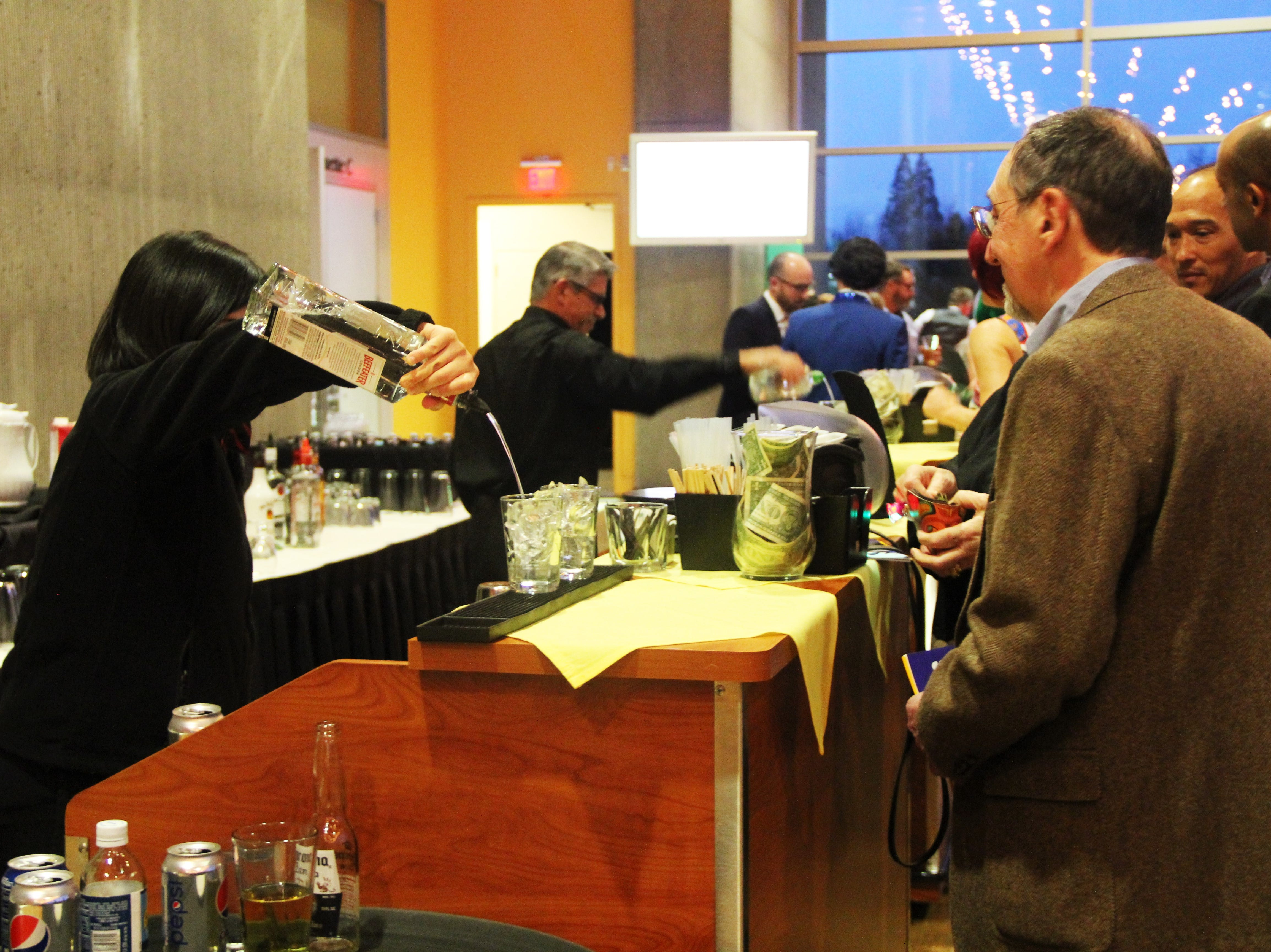 Yeo Ki, banquet supervisor at the Salem Convention Center, pours a drink for a guest at the 20th Annual Clay Ball on Saturday, Feb. 23.