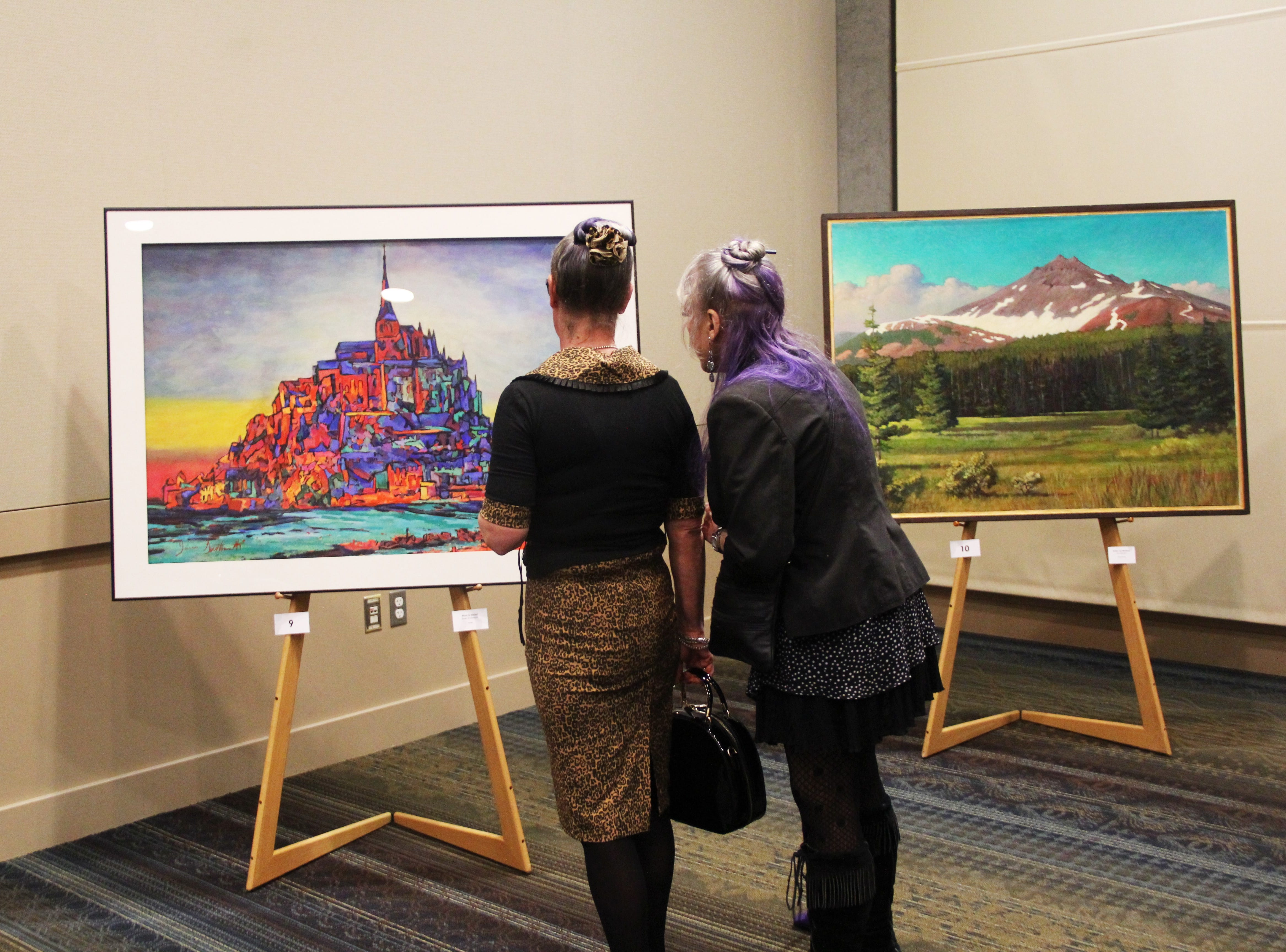 """Carla Paschke, of Salem, and Jo Ann Leadingham, of Keizer, look at """"Mont St-Michel"""" by James Southworth, of Salem, in the live auction room at the 20th Annual Clay Ball on Saturday, Feb. 23."""