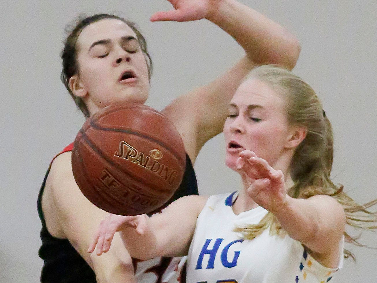 Oostburg's Skylar Ternes (54) and Howards Grove's Leah Parnitzke (10) reach for the ball, Saturday, February 23, 2019, at Howards Grove, Wis.