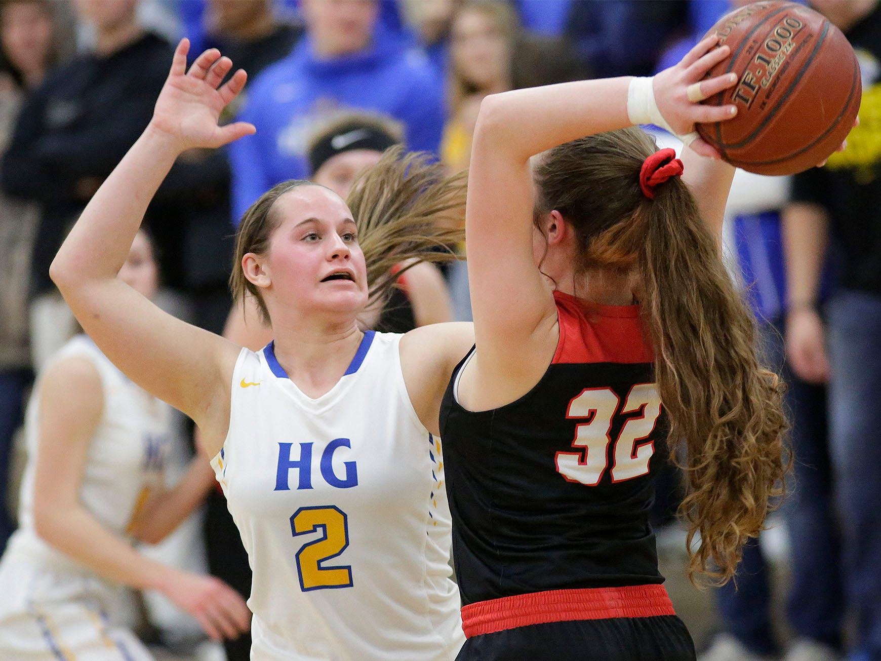 Oostburg's Cambell Van Ess (32) looks to pass the ball beyond Howards Grove's Zayla Mueller (2), Saturday, February 23, 2019, at Howards Grove, Wis.