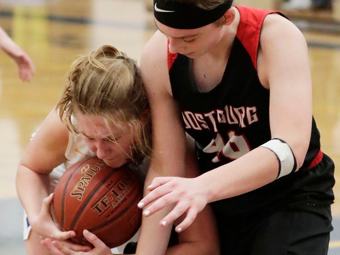 Howards Grove's Kayla Bender (left) grips the ball by Oostburg's Ashley Ternes (40), Saturday, February 23, 2019, at Howards Grove, Wis.