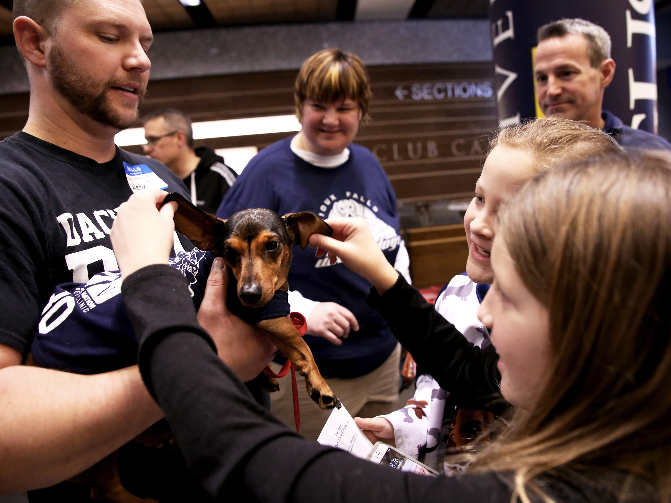 "Weston Thompson lets Makenzie Haack, 10, and Taylor Covrig, 10, pet his dachshund, Riley ""Speedy McSausage,"" during a Stampede game against the Omaha Lancers at the Denny Sanford Premier Center Feb. 23, 2019."
