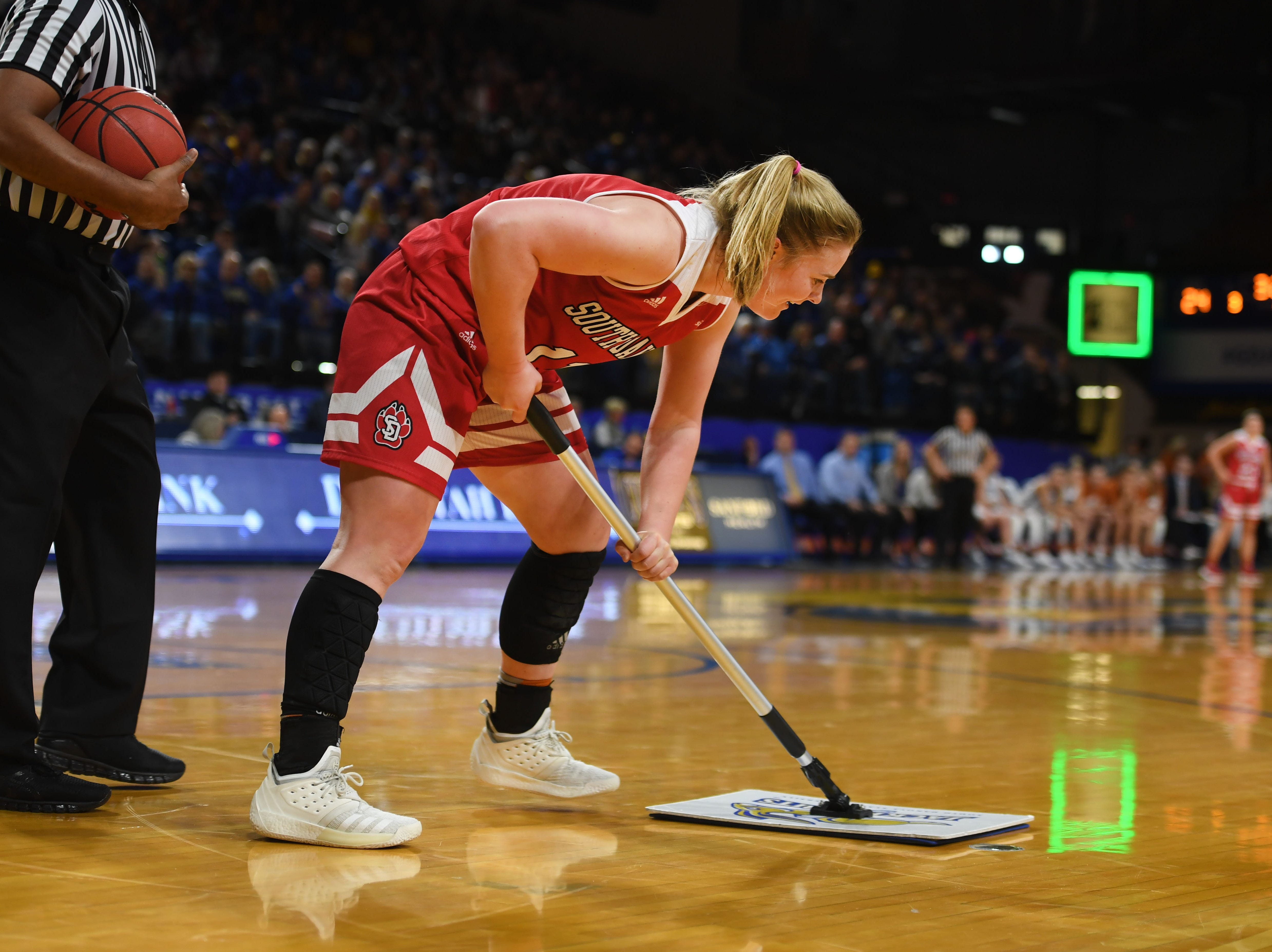 USD's Monica Arens sweeps the floor during the game against SDSU Sunday, Feb. 24, at Frost Arena in Brookings.