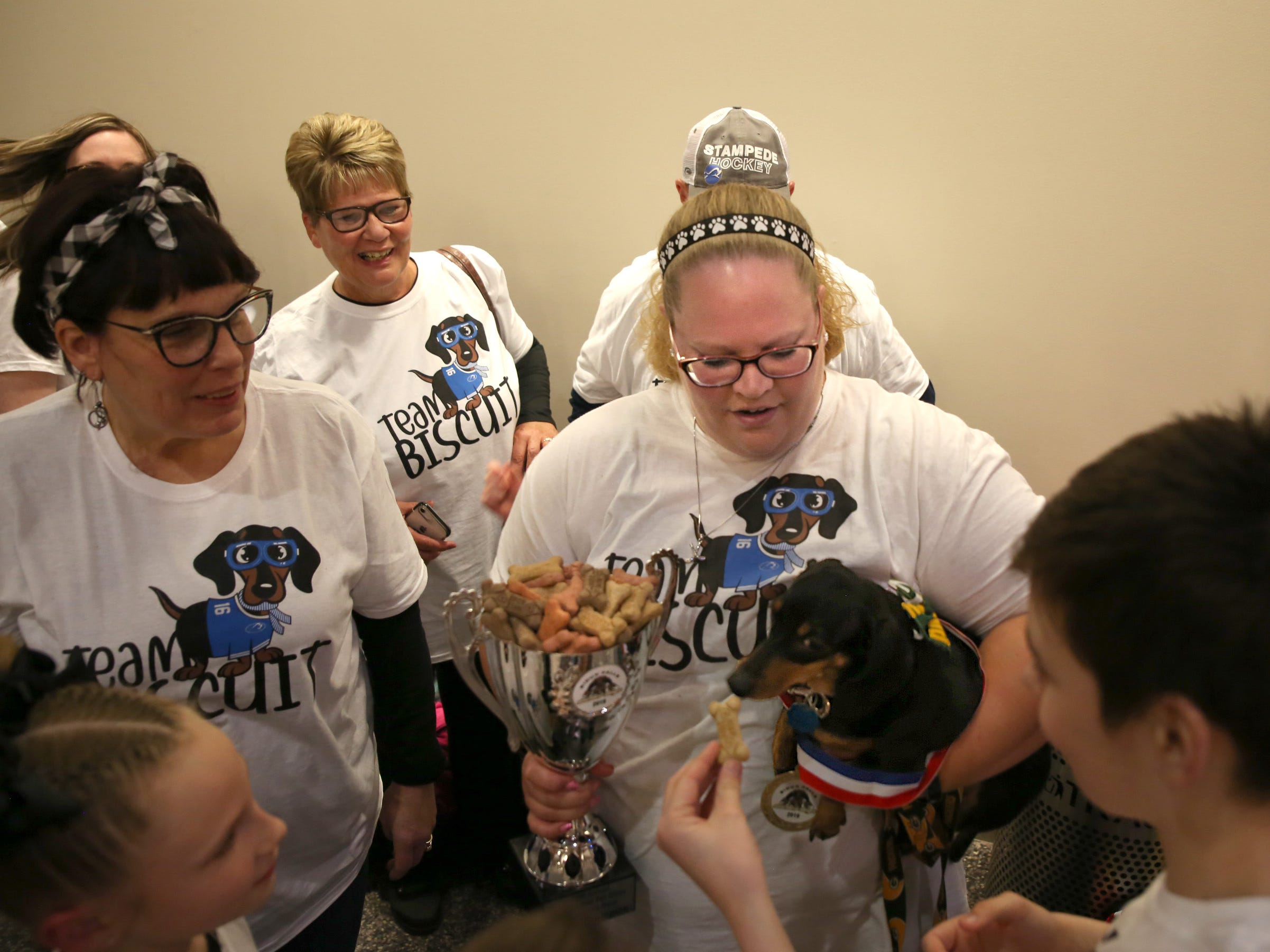 "Supporters sport ""Team Biscuit"" T-shirts after Biscuit won first place at the 12th annual Wiener Dog Races on Feb. 24, 2019. The races took place in front of a sold out crowd during intermission as the Stampede took on the Omaha Lancers at the Denny Sanford Premier Center."