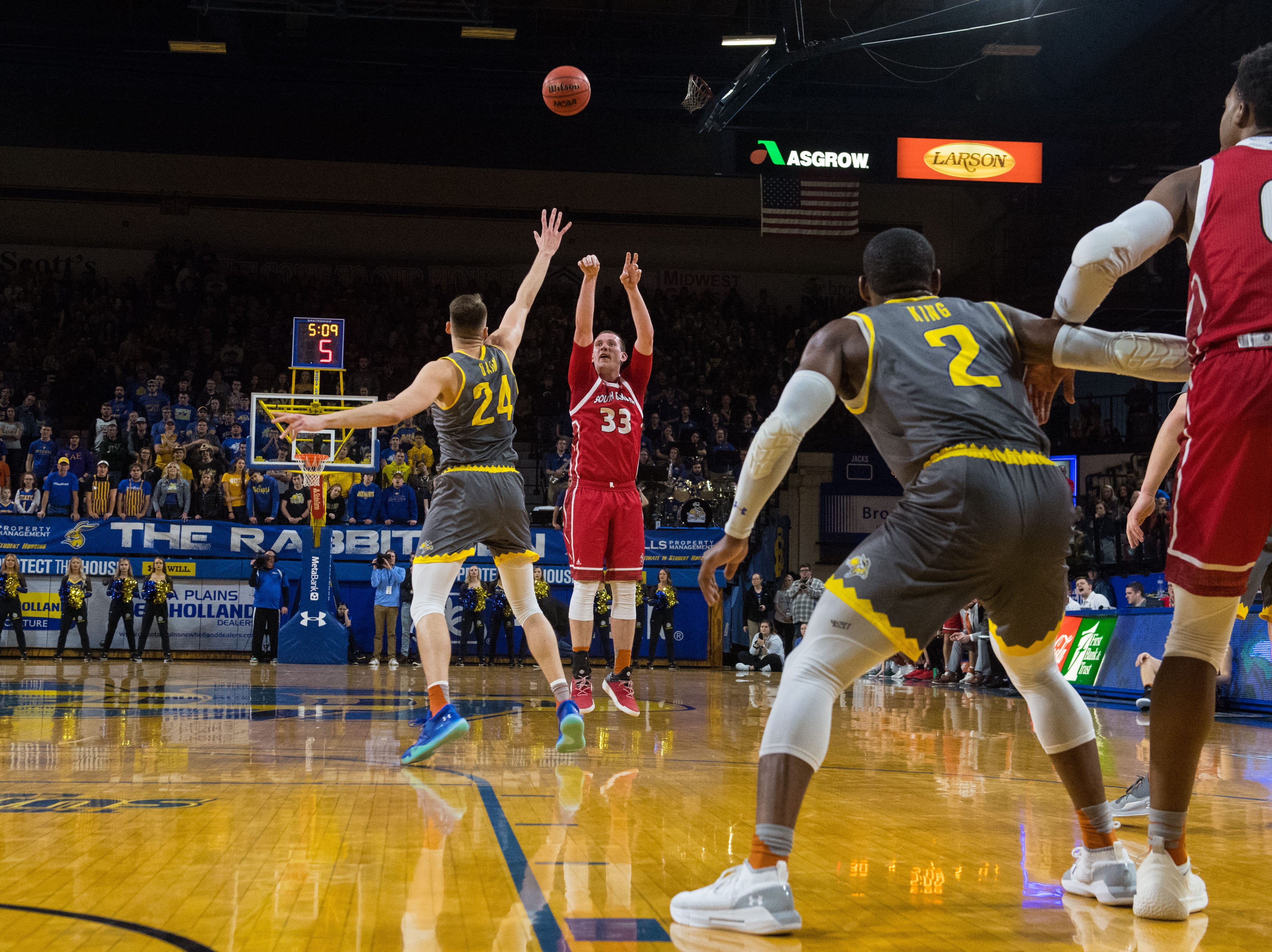 USD's Logan Power (33) shoots the ball over SDSU's Mike Daum (24) during a game, Saturday, Feb. 23, 2019 in Brookings, S.D.