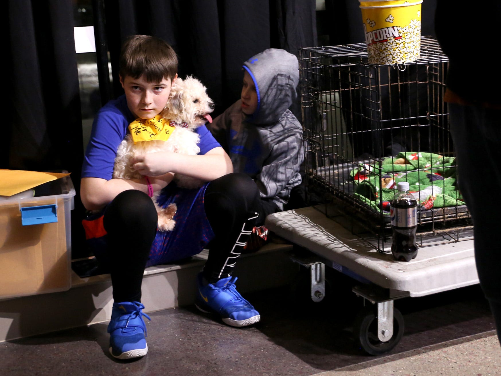 Jacob Underbeg, 12, pets an adoptable dog during a Stampede game against the Omaha Lancers at the Denny Sanford Premier Center Feb. 23, 2019.