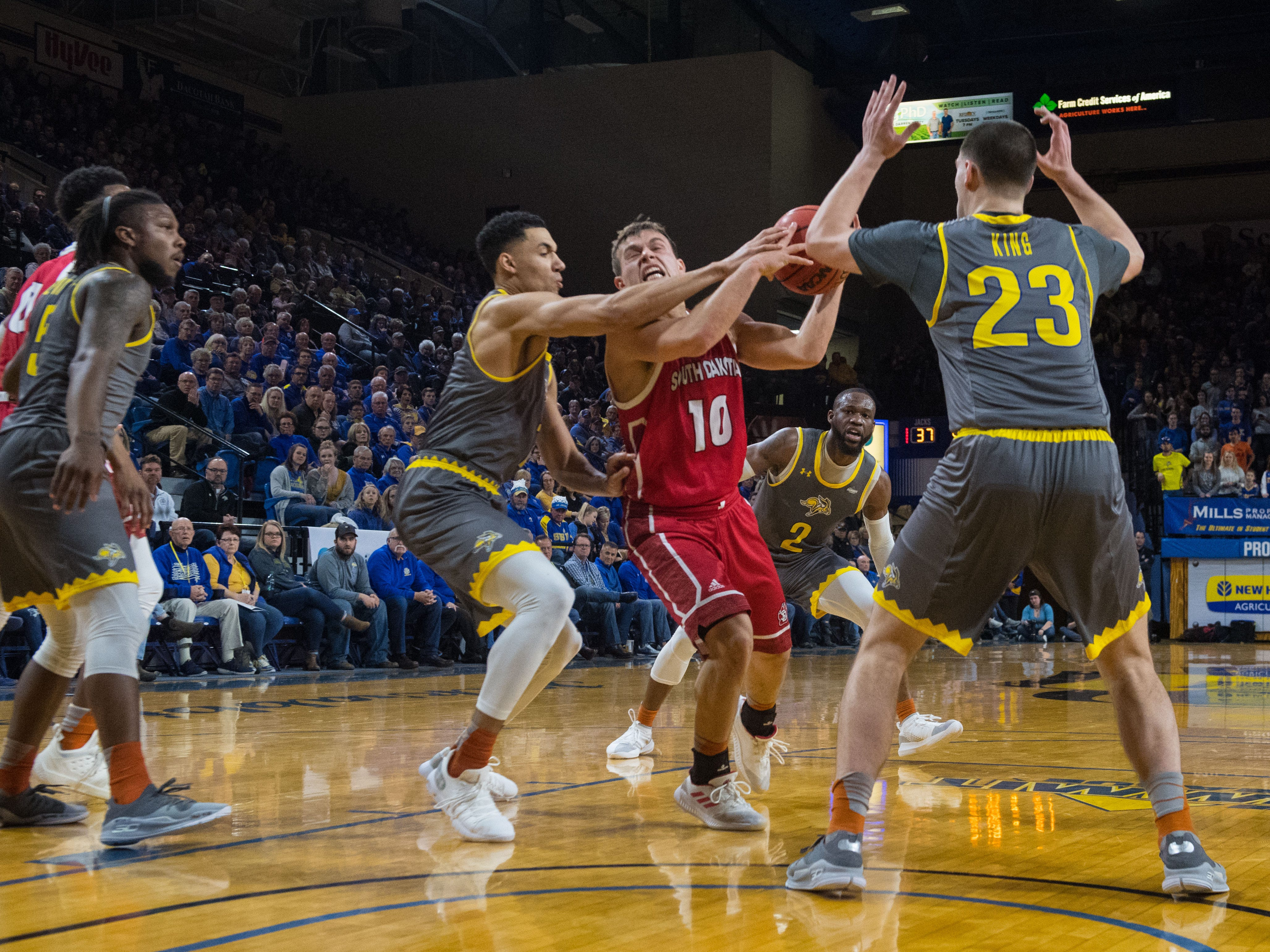 SDSU players block USD's Cody Kelley (10) during a game against SDSU, Saturday, Feb. 23, 2019 in Brookings, S.D.
