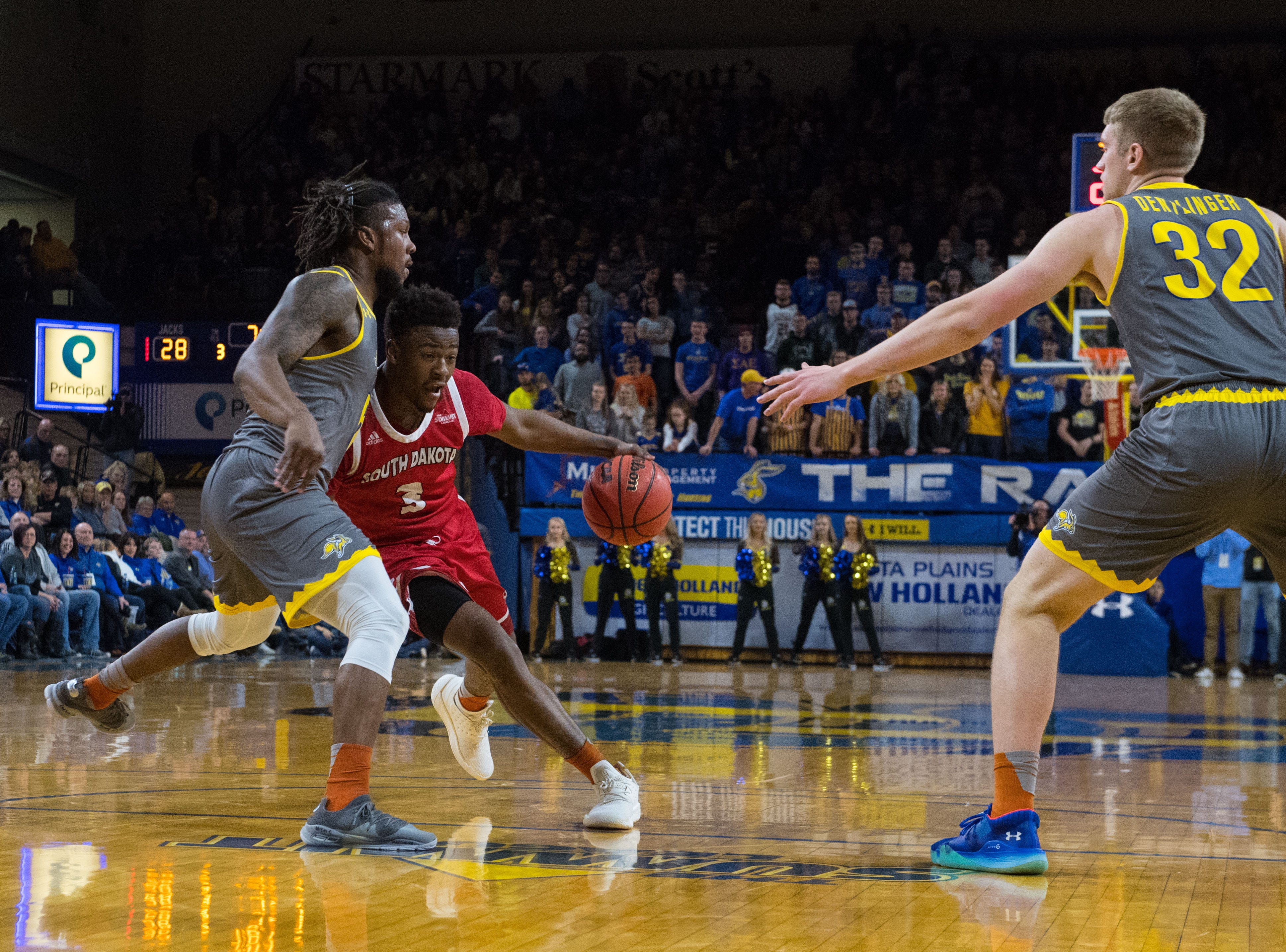 USD's Triston Simpson (3) dribbles the ball past SDSU players during a game, Saturday, Feb. 23, 2019 in Brookings, S.D.