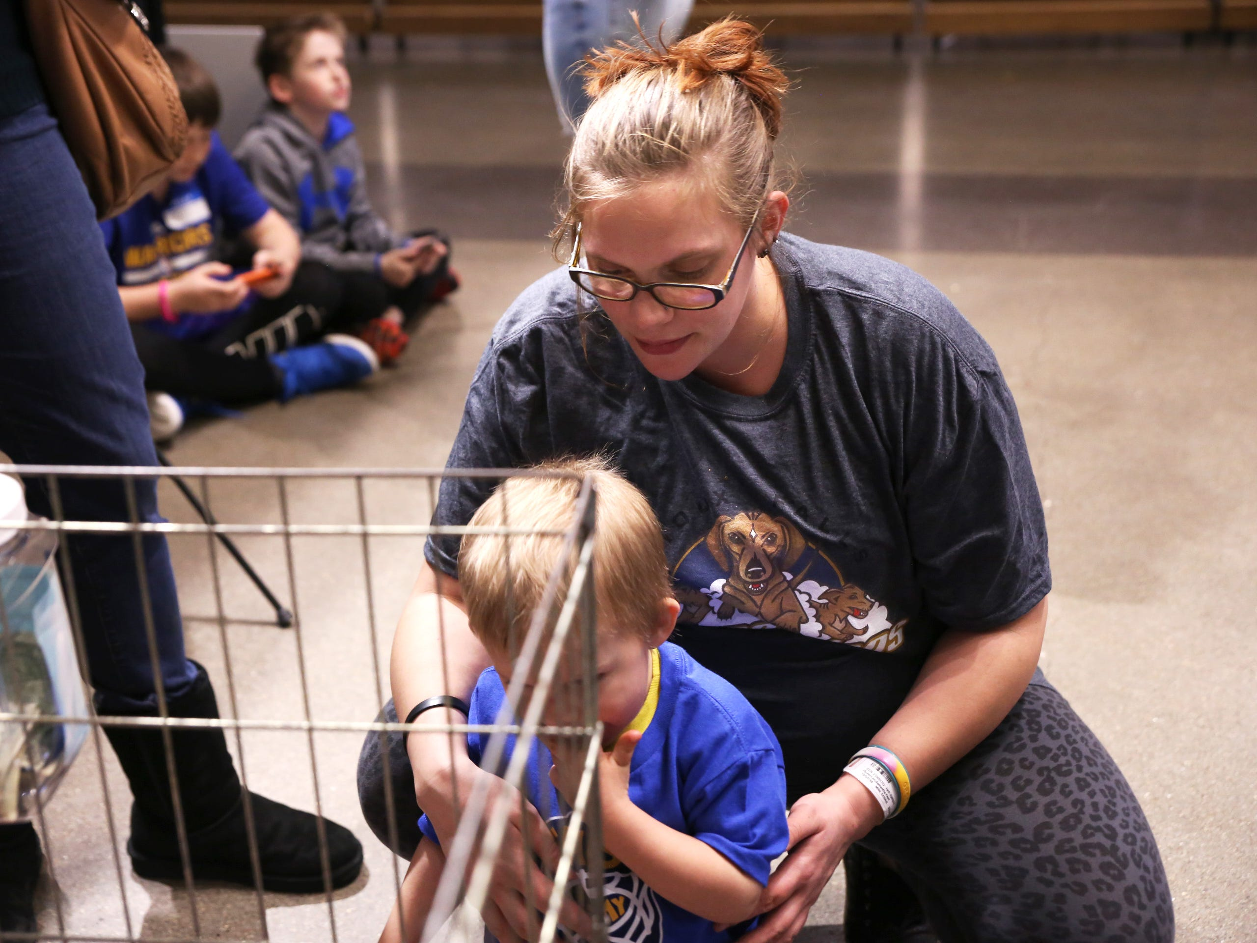 Samantha Sorensen sports a Fighting Wiener Dog T-Shirt that she bought for her son Ashton Hanisch, 3, while they pet adoptable dachshunds during a Stampede game against the Omaha Lancers at the Denny Sanford Premier Center Feb. 23, 2019.