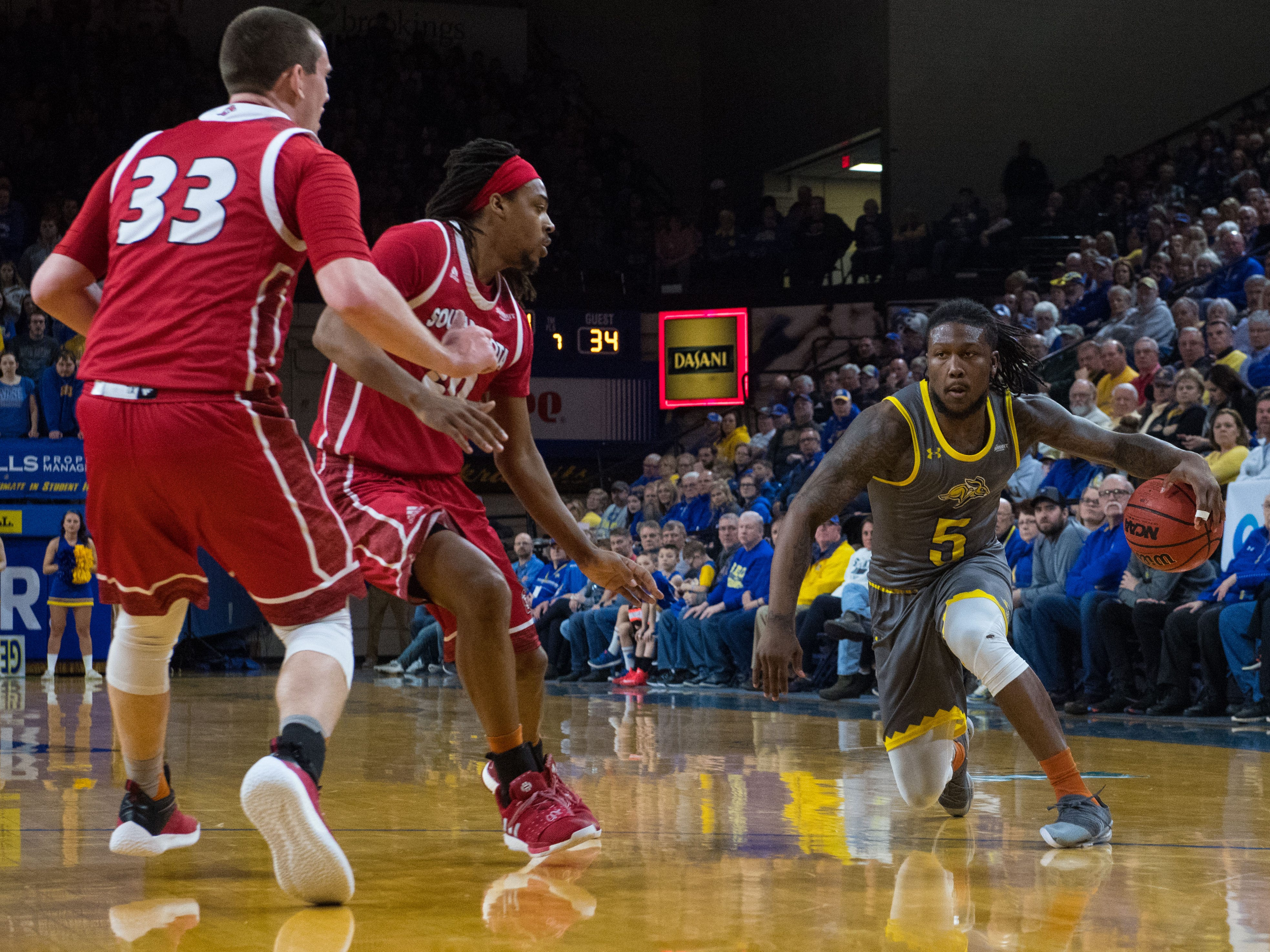 SDSU's David Jenkins Jr. (5) dribbles the ball past USD players during a game, Saturday, Feb. 23, 2019 in Brookings, S.D.