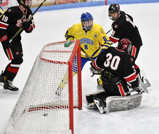 The puck goes into the net in front of Cathedral's Nate Warner during the first period of the Section 6A semifinal game Saturday, Feb. 23, at the MAC in St. Cloud.