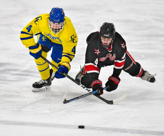 Jon Bell of Cathedral and Eric Johnson of River Lakes struggle for control of the puck during the first period of the Section 6A semifinal game Saturday, Feb. 23, at the MAC in St. Cloud.