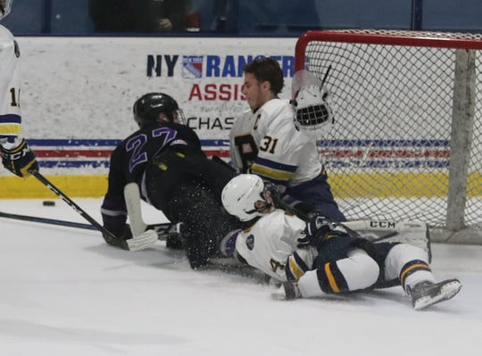 Pelham goalie Liam Ronan loses his helmet after colliding with Jack Browne of John Jay Cross River during the Section 1 Division II championship hockey game at Sport-o-Rama in Monsey Feb. 24, 2019.