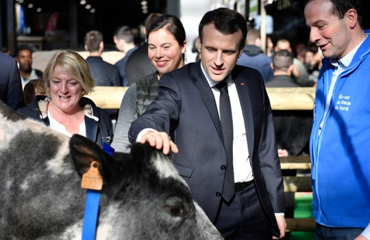 "French President Emmanuel Macron discusses with a breeder as he visits the 56th International Agriculture Fair (Salon de l'Agriculture) at the Porte de Versailles exhibition center in Paris, France, Saturday, Feb. 23, 2019. Macron pledged to protect European farming standards and culinary traditions threatened by aggressive foreign trade practices that see food as a ""product like any other."""
